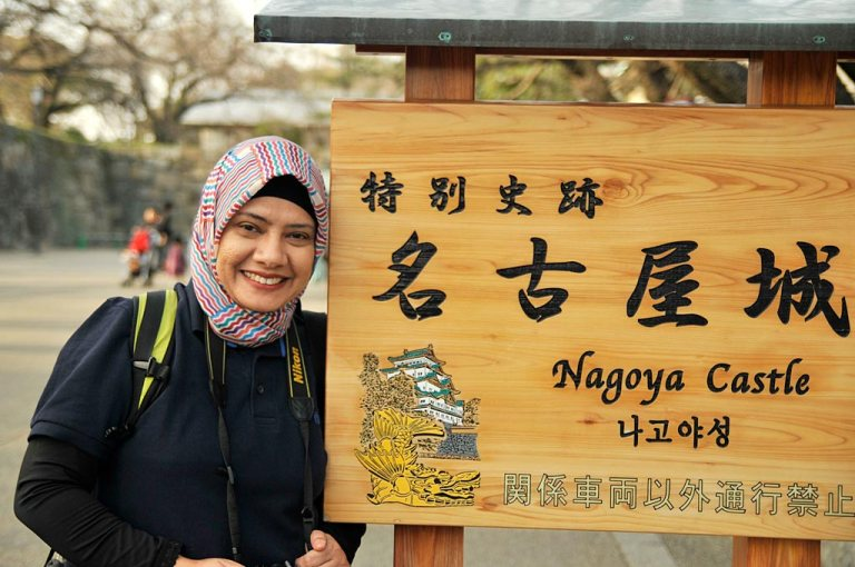 sign-board-eva-nagoya-castle-spring-japan-jepang-travel-trip-gate-stone-woods-hijab-jilbab-trees-green-wall-stand-nikon-street-photography-traveling-best-bench-park-sit-down-seat-grass-bags